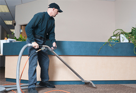 Professional cleaning an office carpet in front of reception desk