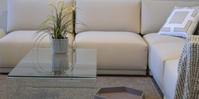 A clean carpet in front of a sofa