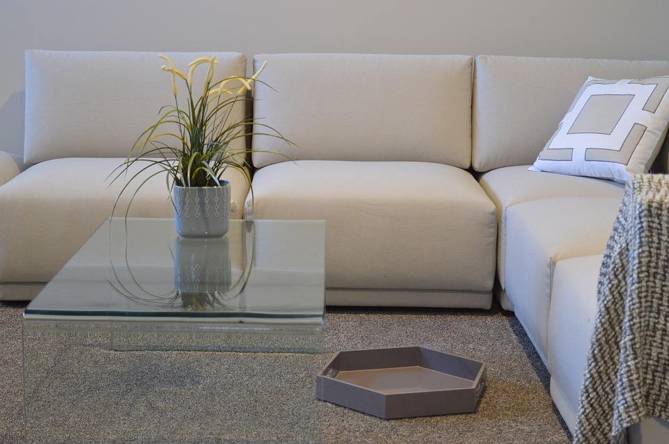 Clean brown carpet in front of cream coloured sofa
